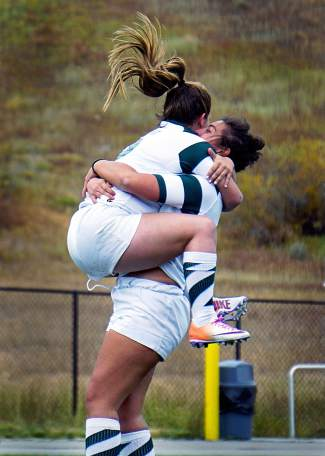 Summit's Lexi Winston, left, jumps into the arms of teammate Jessica Kamins after scoring a try in the Tigers girl's rugby match on Oct. 6, shot by @louietraub