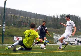 Summit High keeper Noah Glasco makes a play on the ball as teammate Mitchell Gray, right, moves in during first-half soccer action at Tiger Stadium against Colorado Academy Thursday evening. Summit held last year's 3A state champs scoreless in to the second half.
