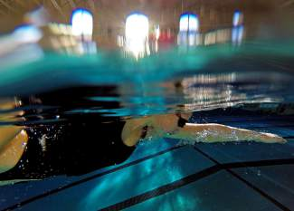 A Summit swimmer cuts through the water during warm-ups before thje Lady Tigers' dual meet at home this week, shot by @louietraub