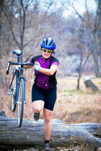 A cyclocross racer hopes over a natural barrier during a cyclocross race.