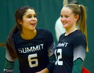 Summit's Michelle Frias (6) talks with fellow senior Kait Akers between sets during a varsity volleyball match against Battle Mountain at home on Oct. 20. The Tigers lost 3-1.