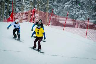 Light snow falls as the women's snowboarder X event takes off at Buttermilk on Sunday afternoon.