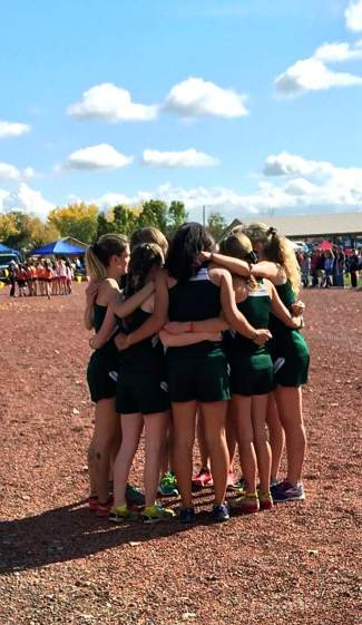 The Summit girl's cross-country team huddles before the 4A league meet in Delta on Oct. 23.