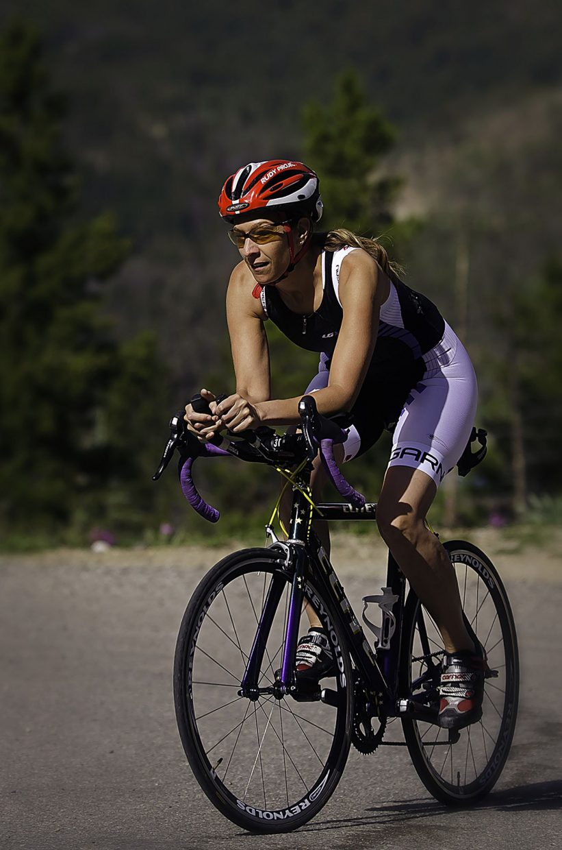 Summit local Candy Elkind trains on County Road 450 in Breckenridge before the Ironman Boulder 70.3 triathlon in July 2013. The 46-year-old Philadelphia native has tackled several Ironman and Olympic triathlons en route to the debut 106 West Triathlon, the first Ironman in Summit County and the only event ever with a swim on Lake Dillon.