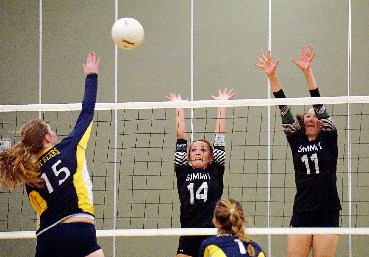 Summit's Anna Mathis (14) and Elle Lyne-Schiffer (11) go up to block a spike by Rifle's Samantha Hinkle (15) during the Tigers 3-0 win over the Lady Bears on Sept. 6.