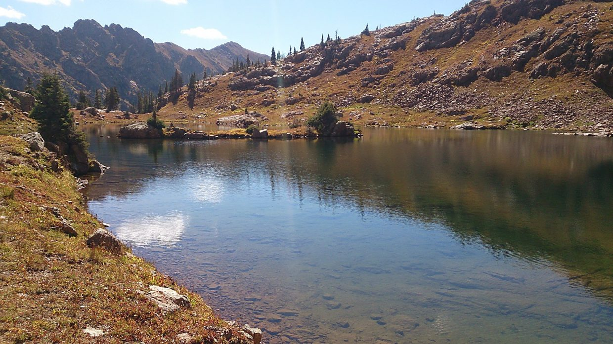 The clear waters of Booth Lake sit idly on a shelf at 11,500 feet and broach the edge of its surroundings peaks on one end and its steep spillway on the other.