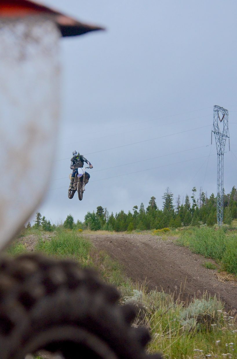Local moto rider Mike Weaver on the jumps at the Tenderfoot MX track just after a rainstorm in early August. Weaver and a small group of volunteers build, maintain and oversee all of the features at the members-only track.