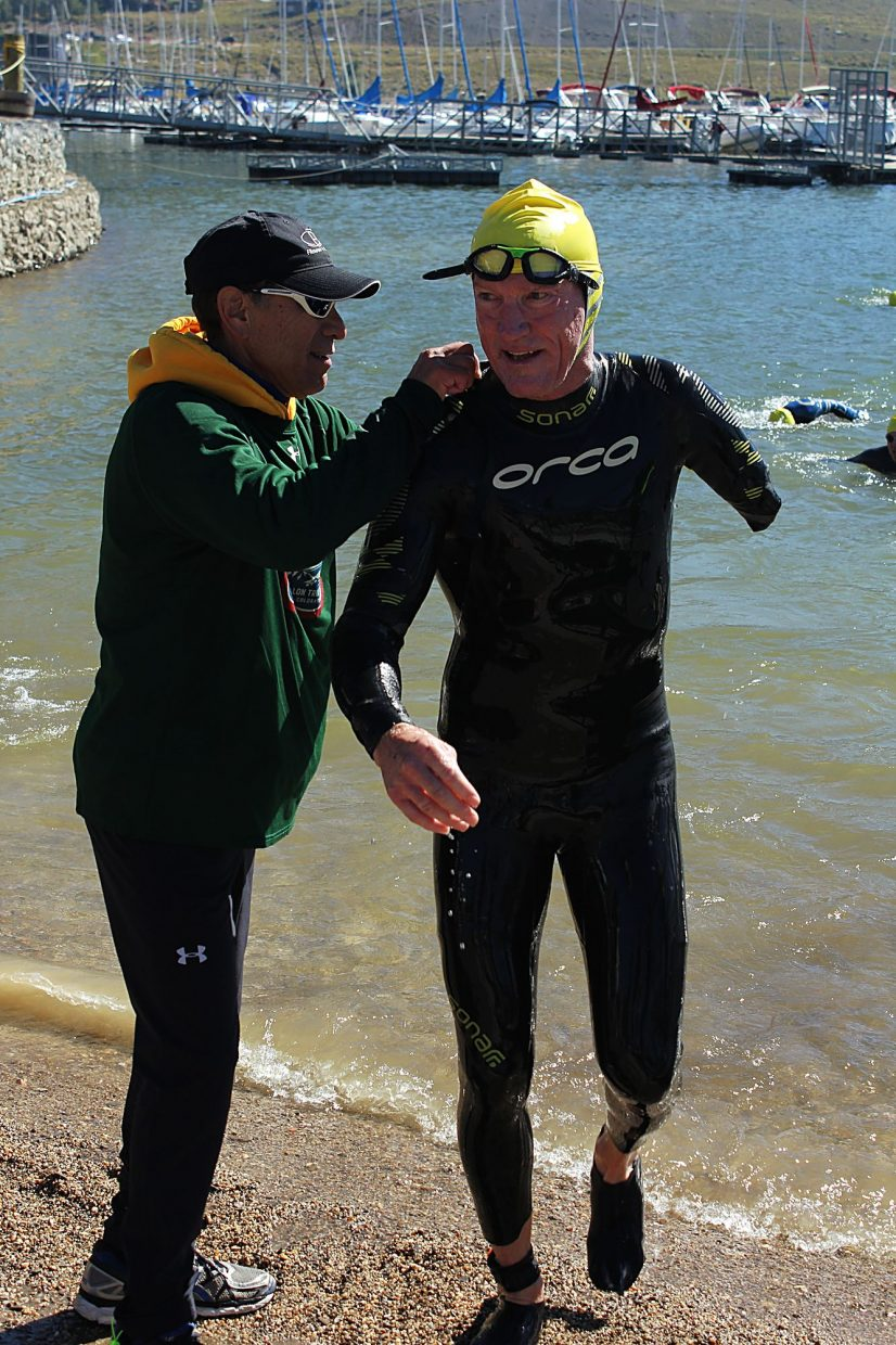 "One of the 106 West volunteers helped ""One-Arm"" Willie Stewart out of his wet suit after finishing the swim portion of the triathlon."