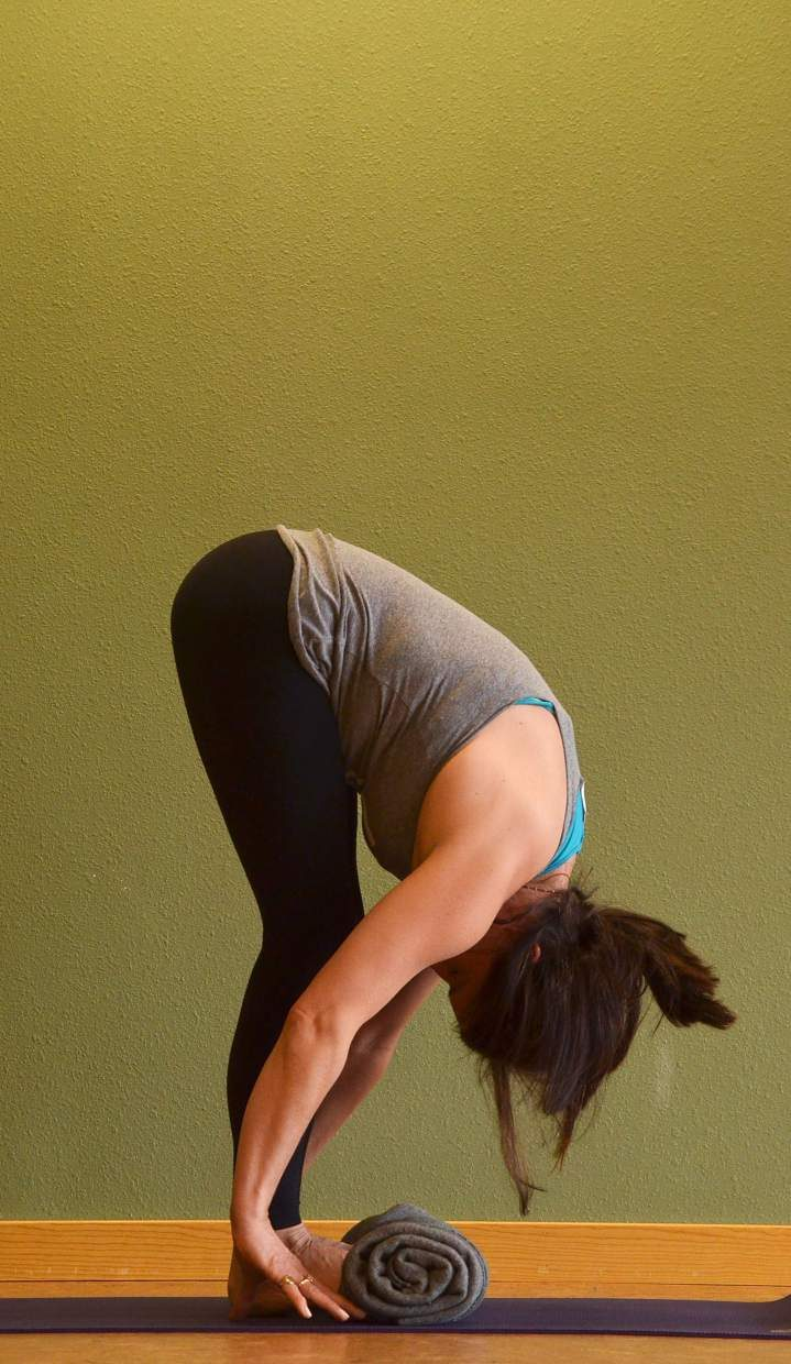 Forward fold with blanket yoga posture for rock climbers.