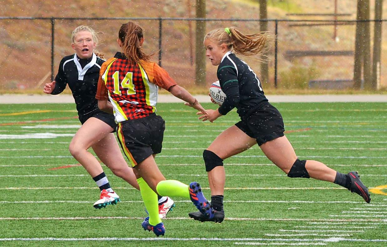 Summit junior Cassidy Bargell (right) and blasts past a Lumberjackies defender with help from a teammate during a home sevens rugby tournament on Sept. 24. Bargell led the Summit Black team to a victory over Chaparral, 33-7, in the final to win the tournament.