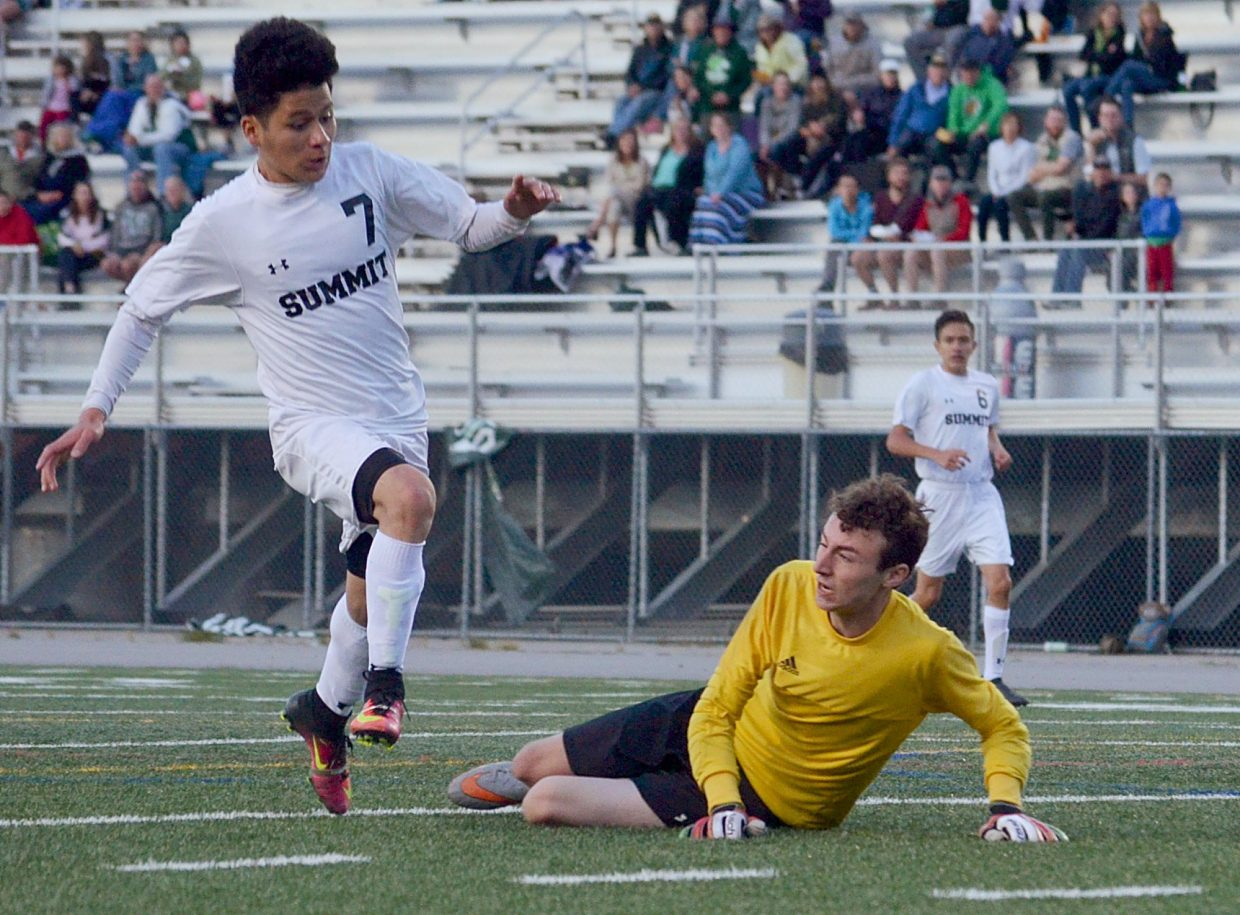 Summit senior forward Gerson Martinez jumps past Conifer goalie Bowen Taylor during the second half of a varsity boy's soccer game at Tigers Field on Sept. 1. The Tigers won, 2-0.