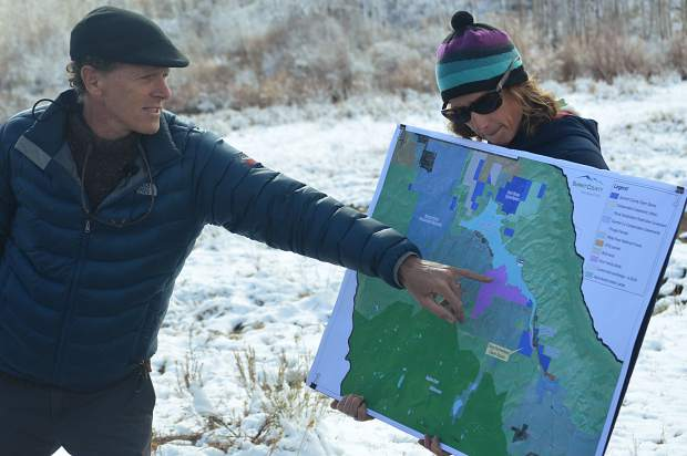 Summit County Open Space & Trails director Brian Lorch points out a feature of the Doig Homestead to onlookers on a topographical map held by department resource specialist Katherine King.
