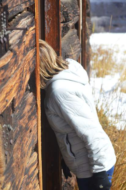 A member of the public field trip explores the interior of the small log cabin located on the Doig Homestead north of Silverthorne.