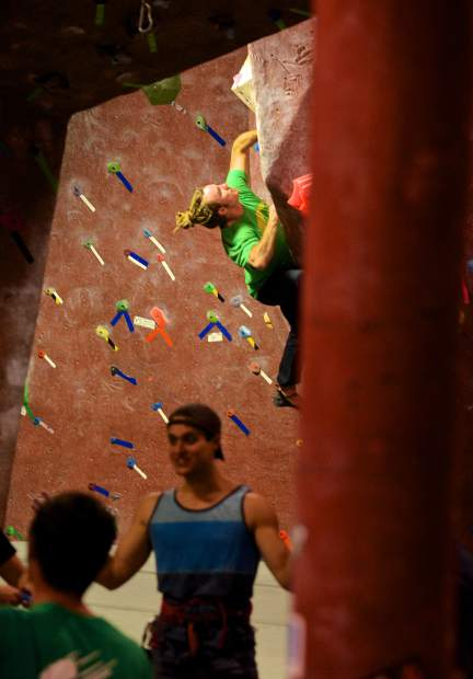 A member at the Summit Climbing Gym looks for his next move on the bouldering wall as fellow members talk near the roped spire. The members-only gym is home to more than 100 bouldering and roped routes, all reset by members every few weeks to keep things fresh.