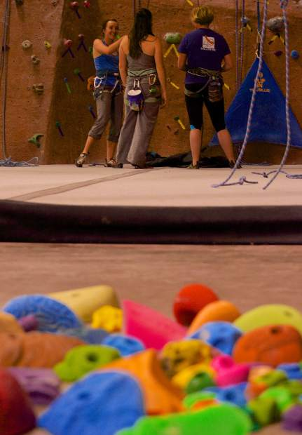 A trio of climbers gets ready to try a route at the Summit Climbing Gym in Silverthorne with recently cleaned holds in the foreground. Members at the co-op gym volunteer for just about every job, from resetting routes to power-washing holds.