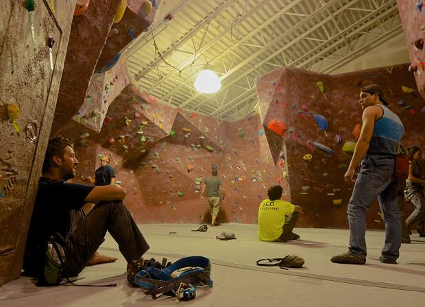 A group of climbers watch as fellow climbers work through problems on the bouldering wall at Summit Climbing Gym in Silverthorne. The gym is home to bouldering routes and roped routes for climbers of all abilities.