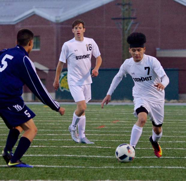 Summit senior forward Gerson Martinez (No. 7) jukes past a Rifle defender as senior midfielder Cole Catron (No. 16) eyes the play during the Senior Night game on Oct. 20. Martinez had two goals in the Tigers 7-1 victory.