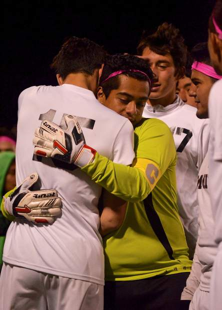 Summit senior goalkeeper Carlos Velasquez (facing) hugs teammate Ty Michalowski (No. 15) during halftime of the Senior Night game on Oct. 20 against Rifle. The Tigers won, 7-1, with Velasquez allowing one goal and Michalowski scoring one.