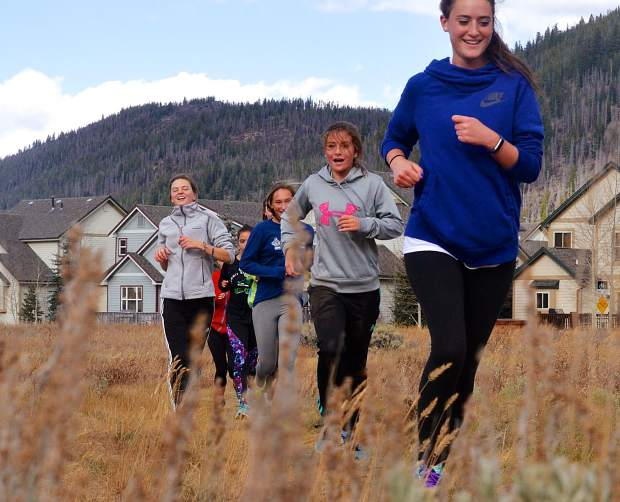 The Summit High girl's cross-country team, led by senior captain Katie Mason (far left, gray coat), during a brief practice the day before 4A XC Regionals on Oct. 19. Mason is the lone senior on this year's team.