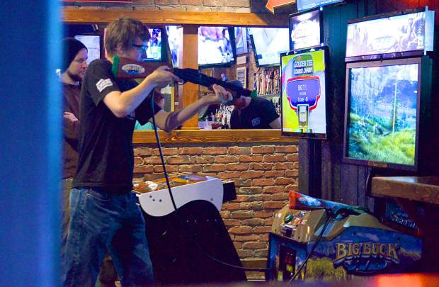 Summit County's Danny Arbuckle (right) practices on the Big Buck HD game in Downstair's At Eric's as the arcade owner, Chris Fadler, looks on. Arbuckle, Fadler and the other arcade owner, Geoff Watson, travel to Austin, Texas this weekend for the 2016 Big Buck World Championships, where Arbuckle hopes to take home the $20,000 grand prize.