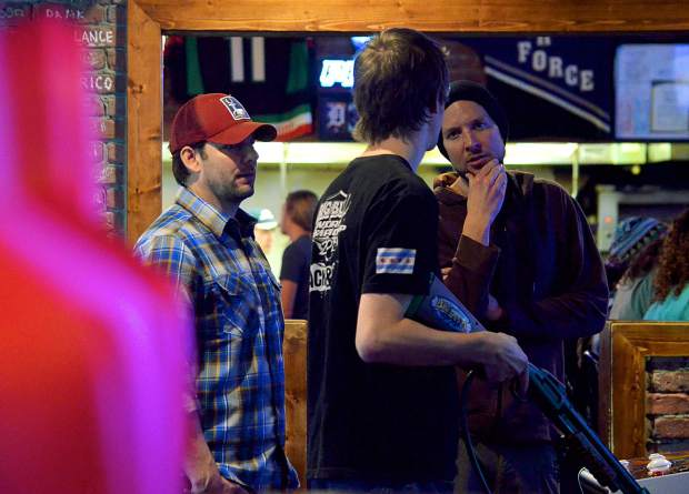 Geoff Watson (far left) and Chris Fadler (far right) watch as Summit County local Danny Arbuckle practices in the Downstairs at Eric's arcade for the 2016 Big Buck World Championship. Arbuckle makes his third trip to the championship on Nov. 5, where he hopes to dethrone current champ, Trevor Gartner, to take home a $20,000 grand prize.