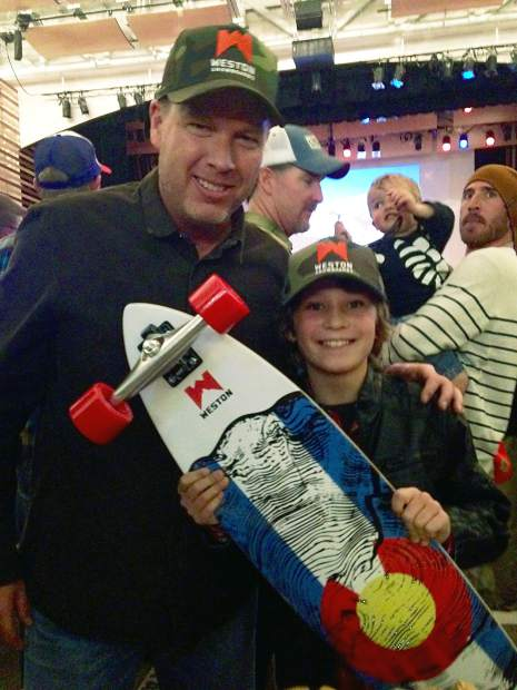 Former Weston Snowboards owner Barry Clark presents a raffle prize to young shredder Liam at the 2014 CAIC Benefit Bash. The Bash returns to Riverwalk Center in Breckenridge this year on Dec. 3.