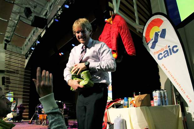 Aaron Carlson, executive director of Friends of the CAIC, throws bags of Vail Mountain Coffee into the crowd at the 2014 CAIC Benefit Bash. This year's event takes place Dec. 3 at the Riverwalk Center in Breckenridge.