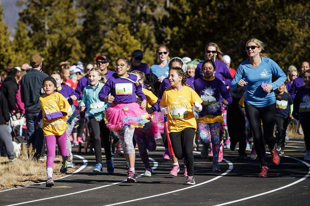 A group of girls and parents runs together near the start line for the Girls on the Run 5K in Frisco on Nov. 12.