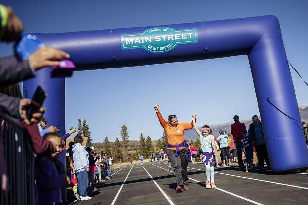 A mom and her daughter celebrate at the finish line for the Girls on the Run 5K in Frisco on Nov. 12. The fun run was the final event of a semester-long program designed to help young girls build a healthy lifestyle.