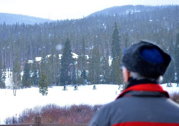 A spectator looks on as riders pedal in the distance during the inaugural Fat Bike Open at Gold Run Nordic Center in December 2015. Fat-bike races across Colorado use Nordic tracks (on frozen golf courses) to get the best conditions for riding.