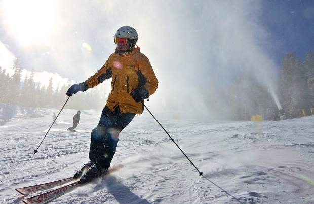 A skier emerges through the spray from a snow gun on Spring Dipper at Keystone Resort on opening day Nov. 18.