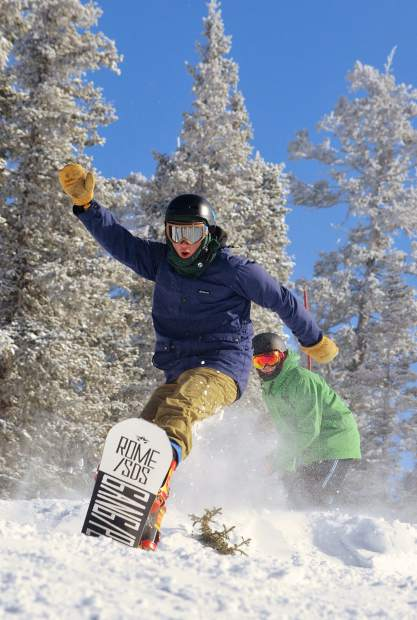 A train of snowboarders launches off snow piles near the top of Dercum Mountain at Keystone Resort for opening day on Nov. 18. The snow was better than expected after 5 inches fell the night before.