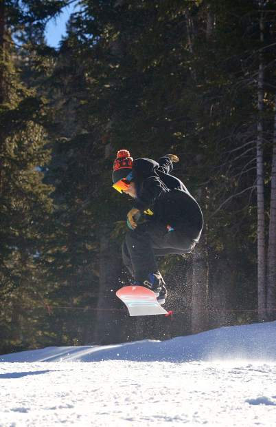 A snowboarder pops an ollie about halfway down Mambo, one of three runs with snow on opening day at Loveland Ski Area Nov. 10. The ski area delayed opening by roughly three weeks to give snowmakers time to blow an 18-inch base from the top of Chair 1 to the base area.
