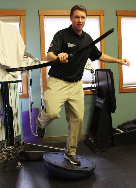 Barton Health athletic Trainer Jeremy Vandehurst balances on a Bosu ball swinging a Bodyblade to demonstrate a balance-related exercise. Gym exercises like single-leg squats and planks build stability, strength and balance for ski and snowboard season.