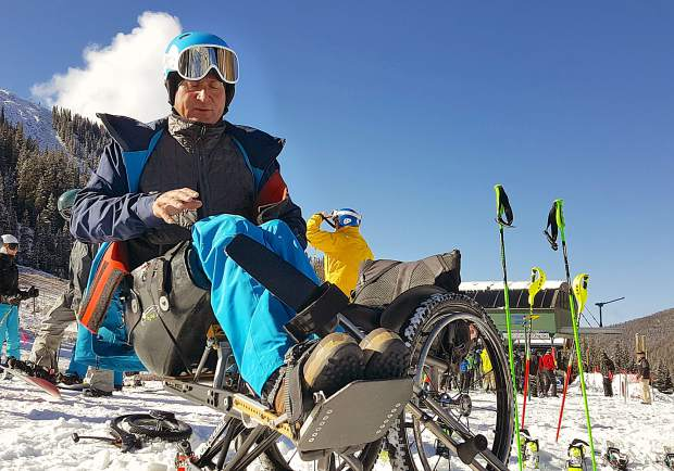 Geoff Krill with the Professional Ski Instructors Association clips into his monoski before taking runs at Arapahoe Basin on Nov. 2. Krill is program director for PSIA's adaptive ski program, which has more than 100 teachers across the U.S.