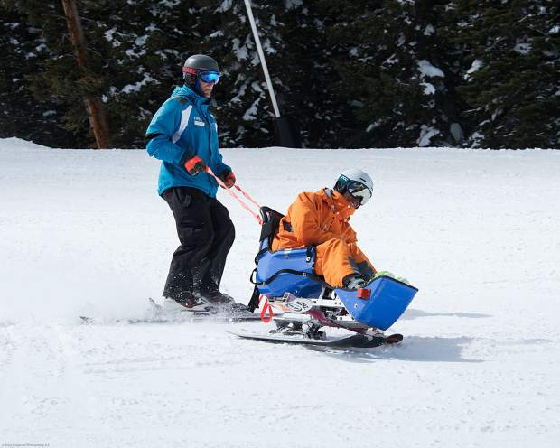 A ski instructor leads a monoski student down the slopes with safety ropes. The Professional Ski Instructors Association has several branches, including monoski instructors and telemark instructors, with a total of 32,000 members across the U.S.