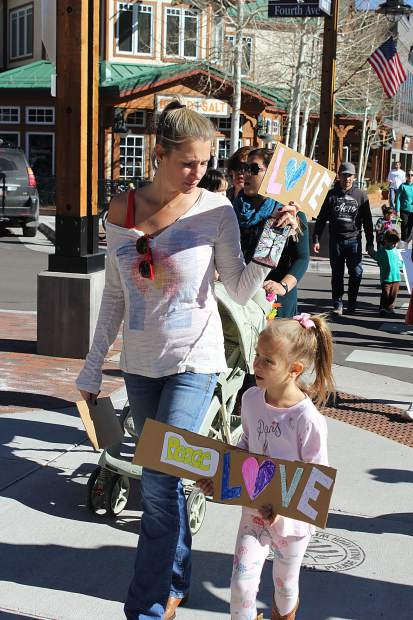 Jacy Ohayon holds her daughter's hand as they walk on Main Street in Frisco as part of a rally organized by Summit County Moms to fight against bullying and discrimination in schools.