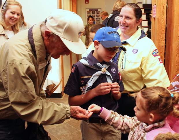 After the flag raising ceremony for Veteran's Day in Silverthorne, the Girl Scouts gave veterans small flag pins.
