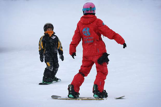 A snowboard instructor at Copper Mountain works with a young client on the learning slope. Instructors recommend mastering the basics on mellow greens before moving to blues, even if the rest of your groups wants to try more difficult terrain.
