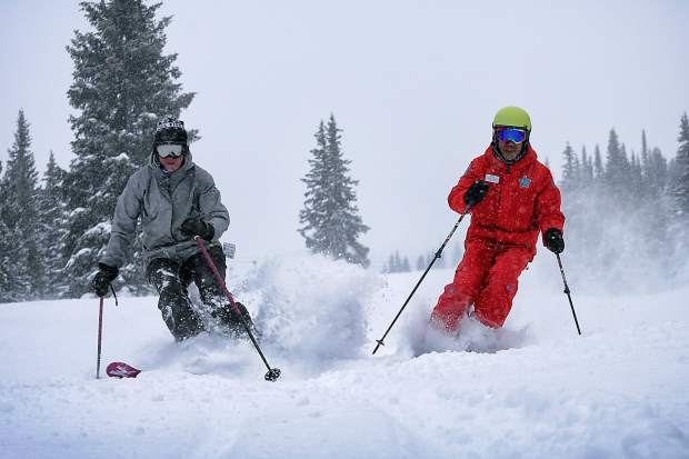 An instructor and student get fresh turns during a powder lesson at Copper Mountain. The resort offers several lessons for advanced and expert students, including advanced instruction for riding deep powder on skis made for backcountry conditions.
