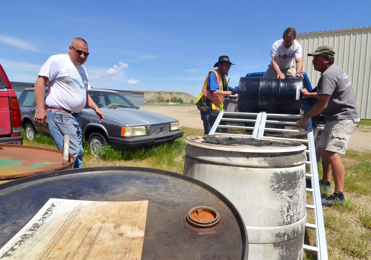 A group unloads massive barrels of airshow smoke oil at the Kremmling Airport before the Dillon Airshow on June 11.