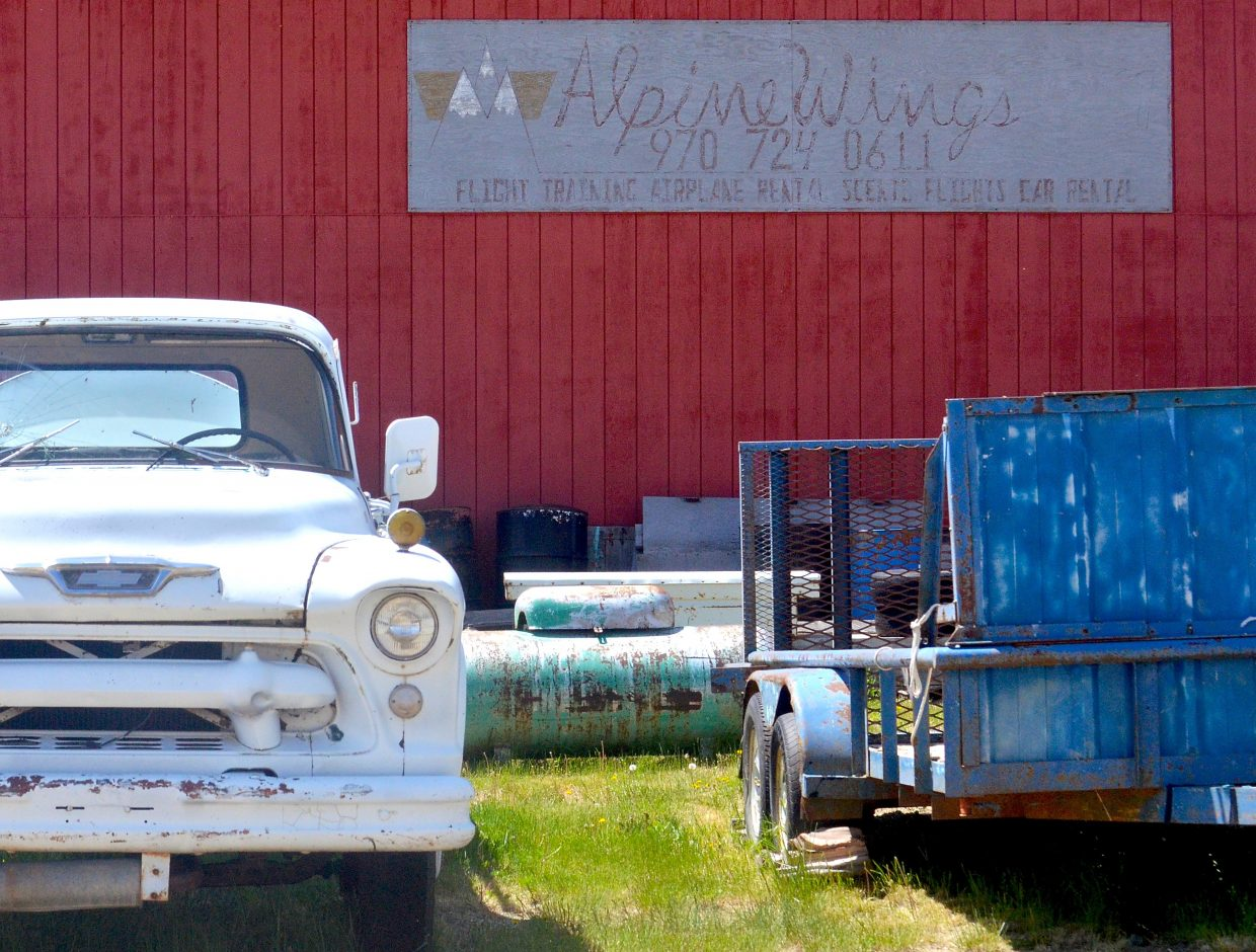 An old gas truck and trailer parked outside the lone office building at the Kremmling Airport.