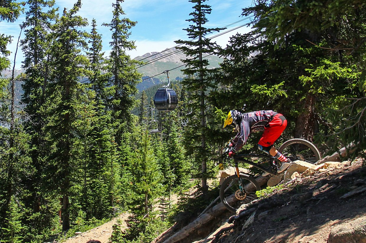 Summit Cove resident Nick Baker drops out the bottom of Jam Rock, an intimidating boulder garden and one of the signature features at Keystone Bike Park.
