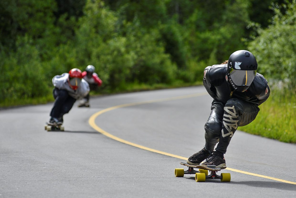 Downhill longboarders tuck low through a turn on the western side of Vail Pass.