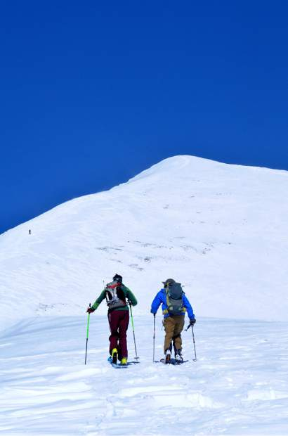 Colorado backcountry skiers Teague Holmes (left) and Fritz Sperry with Quandary Peak (14,265 feet) looming high in the distance. The trek is 5.2 miles roundtrip, including a nearly 3-mile uphill skin covering 3,415 vertical feet before several descent lines of 3,000-plus vertical feet.