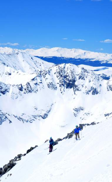 Teague Holmes (left) and Fritz Sperry wait for the final member of their ski group in a stable zone of the Cristo Couloir, a popular ski line from the summit of Quandary Peak (14,265 feet).
