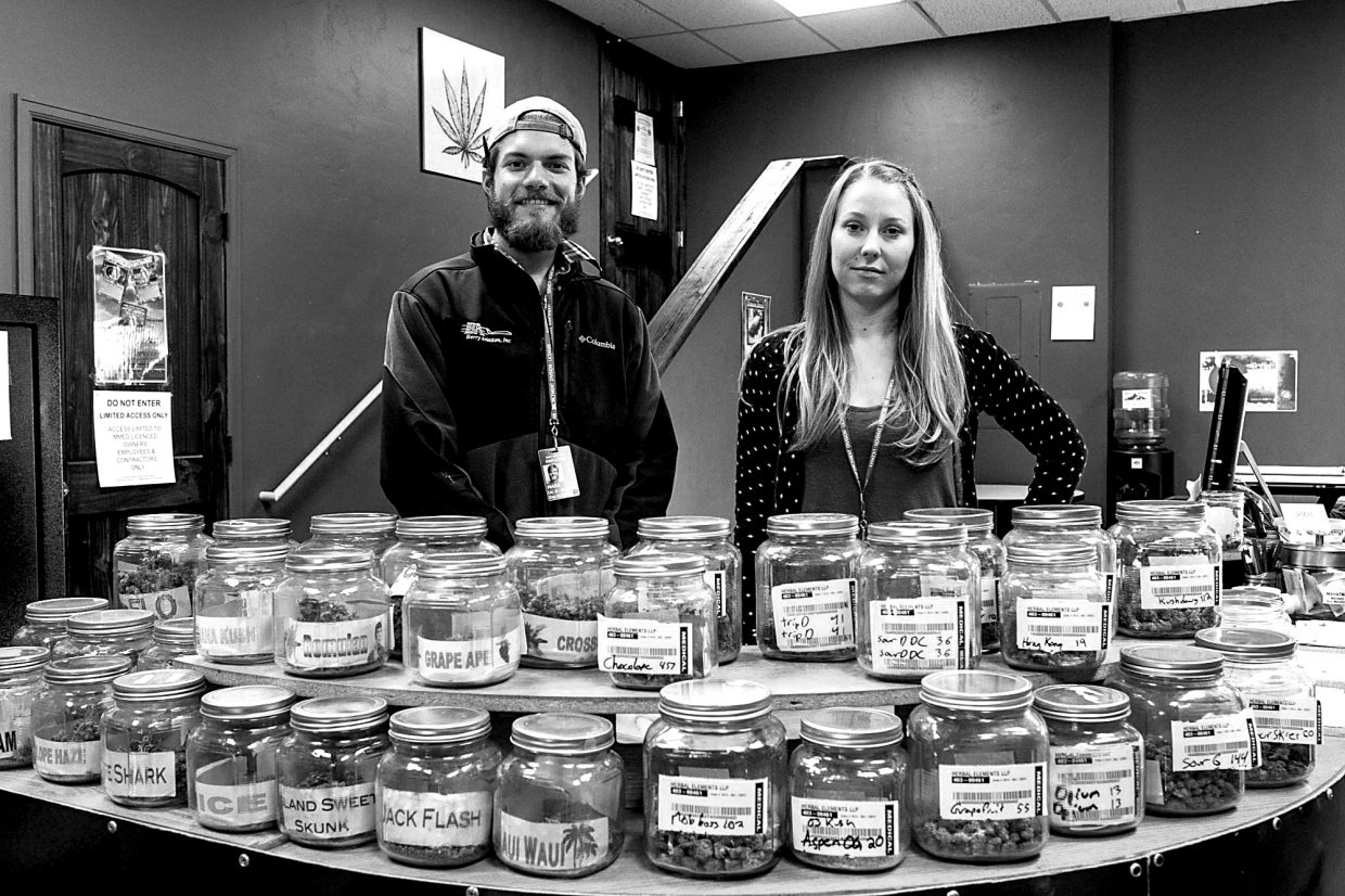 Herbal Elements employees Mark Boutan and Rachel Crow stand in front of an impressive selection of Marijuana in Eagle-Vail on Tuesday. d