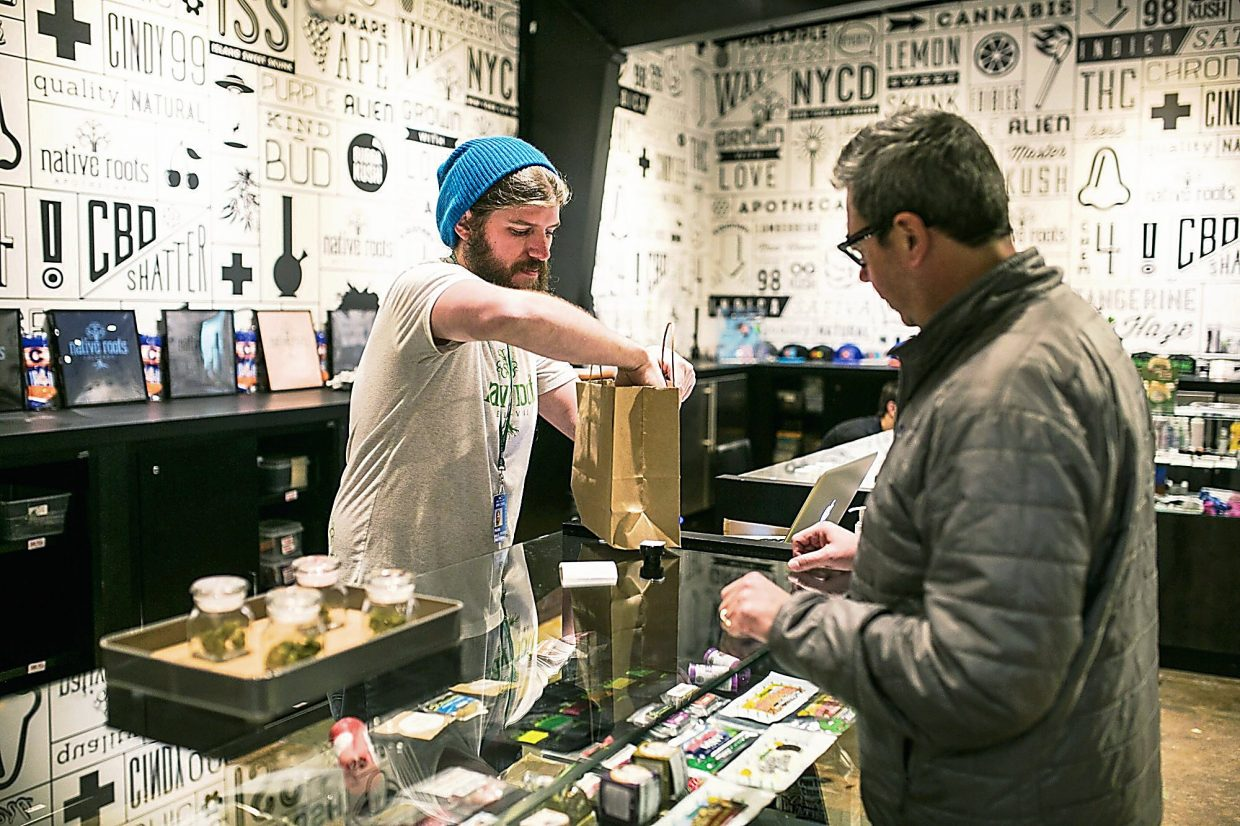 Native Roots employee Mark Petrina helps Claudio Campos of Edwards with the purchase of recreational marijuana in Eagle-Vail on Tuesday. g