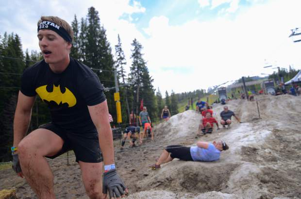 Competitors at the inaugural Breck Spartan in June 2015 crawl over a mound of snow for the final set of obstacles at the base of Peak 9. The race returns today with a new set of obstacles and competitors vying for title of Spartan champion.