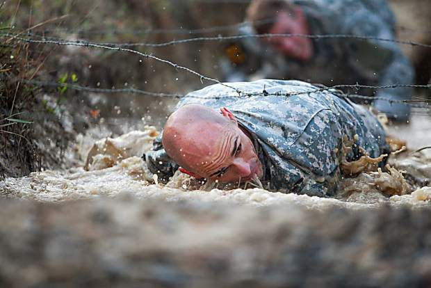 U.S. Army Green Beret Robert Killian crawls through water beneath a bed of barbed wire during a recent military competition. The Carolina native and current Longmont resident is the reigning Spartan World Champion and comes to the Breck Spartan this weekend in hopes of retaining his crown.